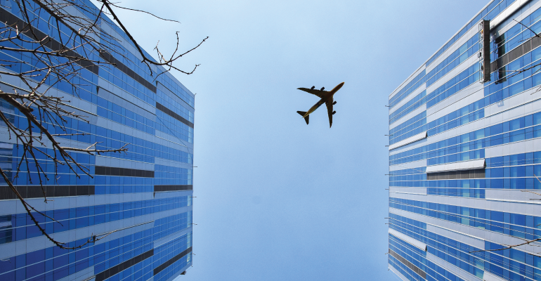 airplane flying overhead two skyscrapers