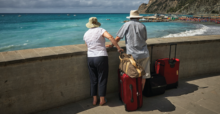 elderly couple with luggage looking at the ocean